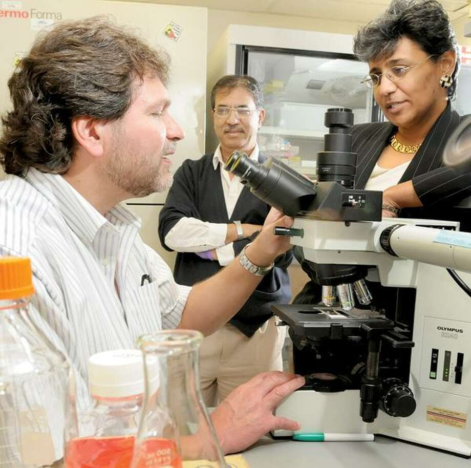 Peter Hvizdak/Register photo, Michael P. DiGiovanna, M.D., Ph.D., associate professor of Medicine and Pharmacology and the co-director of the Breast Cancer Research Program; Ashok Chakraborty, research scientist in the Breast Cancer Research Program; and Dr. Anees B. Chagpar, director, Yale Breast Center at Smilow Cancer Hospital in the breast cancer research lab.