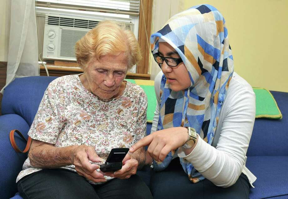 New Haven - 96-Year-old Phyllis Matziotti uses a cell phone for the first time in her life as 15-year-old Emine Demir gives her a lesson on the use of the technology at the East Shore Senior Center .  Photo by Peter Casolino/New Haven Register