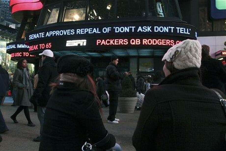 "Cassandra Melnikow, foreground left, and her sister Victoria Melnikow, right, sit in New York's Times Square as news of the Senate approving the repeal of ""Don't Ask Don't Tell"" is displayed outside ABC Television's Times Square studios Saturday Dec. 18, 2010. (AP Photo/Tina Fineberg) Photo: AP / FR73987 AP"