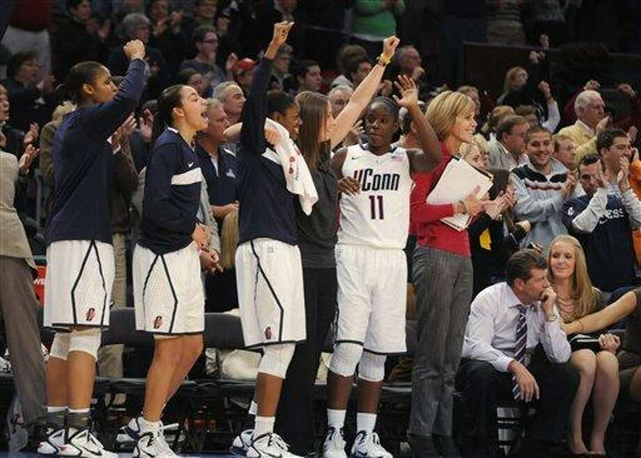 Connecticut celebrates in the final seconds of its 81-50 win over Ohio State in an NCAA college basketball game in the Maggie Dixon Classic at Madison Square Garden in New York, Sunday, Dec. 19, 2010.  (AP Photo/Henny Ray Abrams) Photo: AP / FR151332 AP