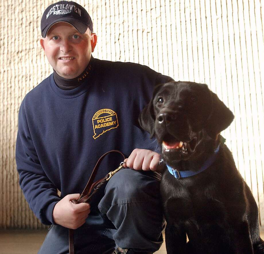 """Photo-Casolino Officer Robert Fumiatti with the department's drug dog """"Major"""" in this November 2003 file photo."""