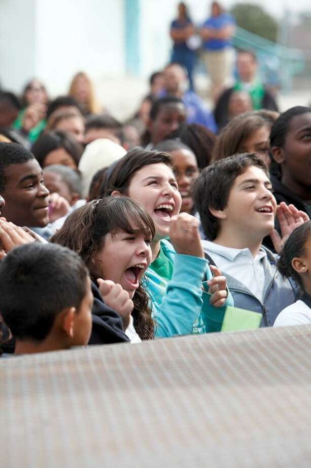 "Students cheer as the show's hosts announce the makeover from the back of a truck on the Compton school's ballfiend in ""School Pride."" NBC photo."