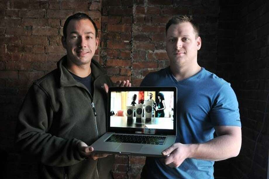 """David Salinas, left, and Peter Sena II, founders of Digital Surgeons, hold a laptop playing their Starbucks video parody of """"Beamer, Benz or Bentley"""" by Lloyd Banks. (Peter Casolino/Register)"""