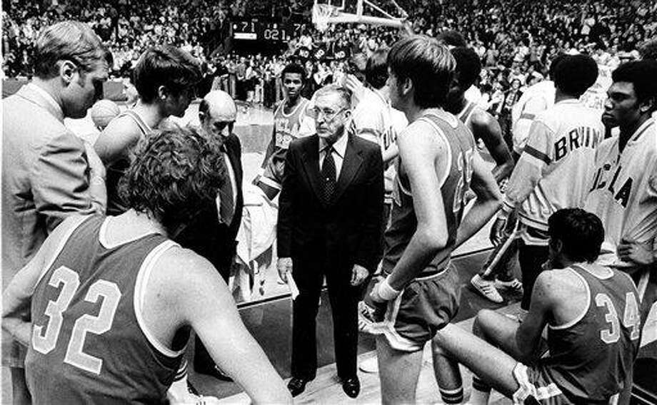 FILE - This Jan. 19, 1974, file photo shows UCLA basketball coach John Wooden, center,  during the last time out against Notre Dame, in South Bend, Ind. At left foreground is Bill Walton (32). The date the streak ended is burned in Walton's memory. He spits it out with distaste when asked what he recalls most about UCLA's NCAA-record 88-game winning streak.  (AP Photo/File) Photo: AP / AP1974