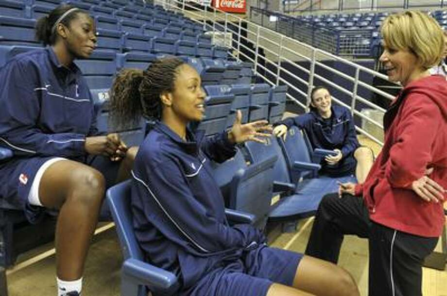 UConn women's assistant head coach Chris Dailey talks to freshmen Samarie Walker, left, and Machala Johnson as teammate Kelly Faris looks on during media day Wednesday in Storrs. (Associated Press/Jessica Hill) Photo: AP / FR125654 AP