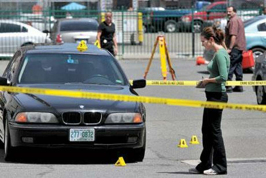 Investigators work Saturday at the scene of a homicide in a Crown Street parking lot, where a man was shot early Saturday after leaving a nightclub. (Peter Casolino/Register)