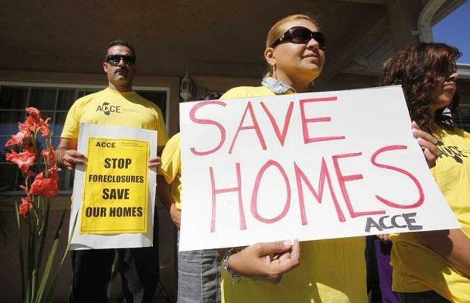 In this Sept. 24, 2010 photo, supporter Marisa Salas, right, holds a sign during a foreclosure and eviction rally at the home of Carlos Moreno in Menlo Park, Calif. Moreno has owned his home since 2006, had his home under foreclosure since January 2010, and was served eviction notice in July 2010. His case is now pending with the bank. For most Americans at risk of losing their homes, the brutal business of foreclosure goes on. (AP Photo/Paul Sakuma) Photo: AP / AP