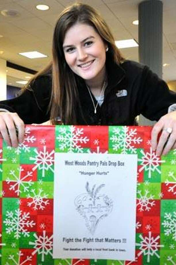 QU student Kirsten Owens poses with one of the West Wood School food drop boxes at Peoples Bank at 3496 Whitney Ave. for the West Wood Pantry Pals to benefit the Hamden Food Bank. VM Williams 12.13.2010