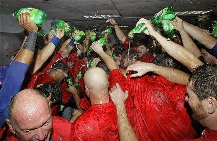 Texas Rangers players douse teammate Josh Hamilton with ginger ale following the team's 5-1 win over the Tampa Bay Rays in Game 5 of baseball's American League Division Series in St. Petersburg, Fla. The Rangers advanced to the AL championship series against the New York Yankees. (AP Photo/Chris O'Meara) Photo: AP / AP