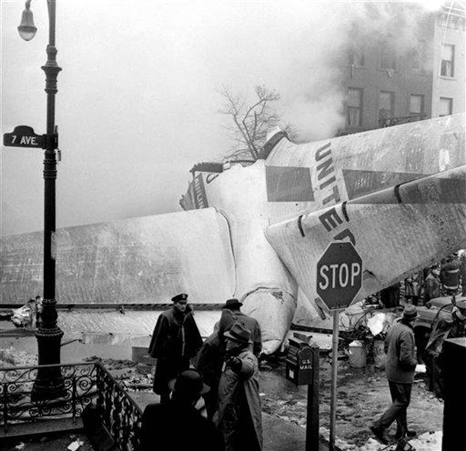 In this Dec. 16, 1960 file photo, authorities surrouned the remains of a United Air Lines jet at Seventh Avenue in Brooklyn where it crashed after colliding with a TWA propeller plane one mile above New York City. Fifty years ago it was the deadliest air disaster up to that time, resulting in the deaths of all 128 people on both aircraft, and six on the ground. (AP Photo/File) Photo: AP / AP1960
