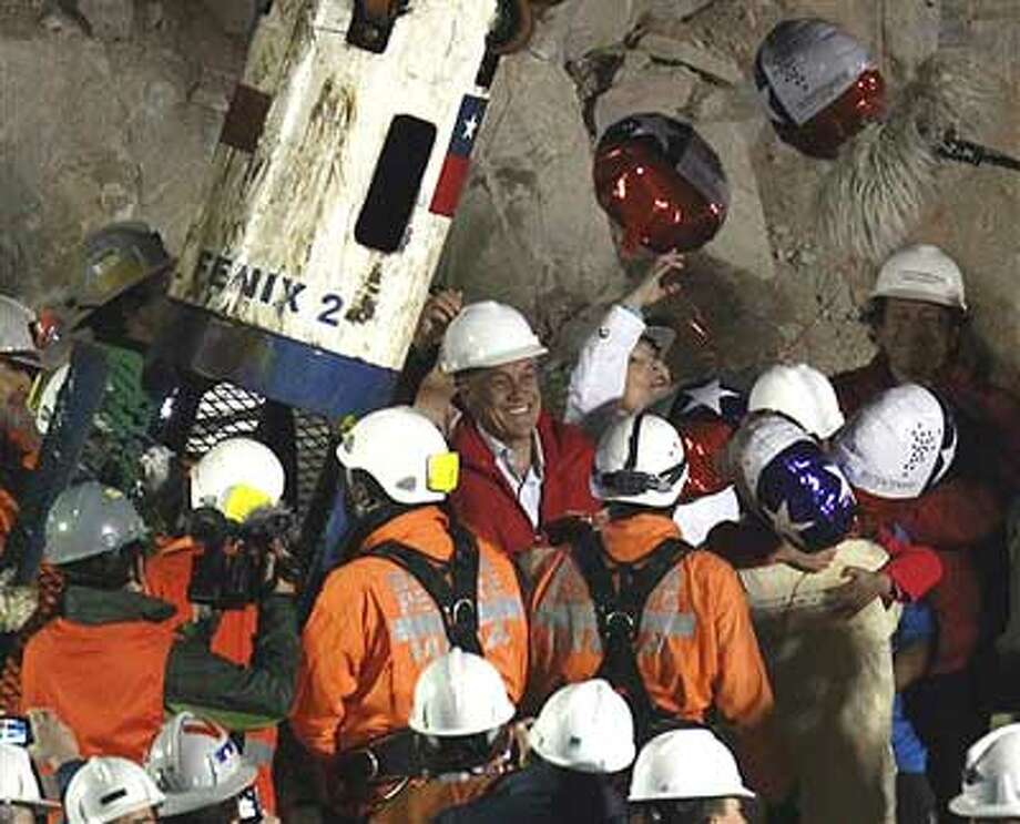 Chile's President Sebastian Pinera, center, smiles as miner Pedro Cortez, bottom right, is greeted by his family after being rescued from the collapsed San Jose gold and copper mine where he had been trapped with 32 other miners for over two months near Copiapo, Chile, Wednesday Oct. 13, 2010. (AP Photo/Roberto Candia)