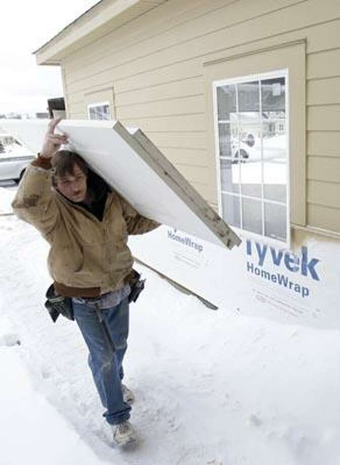 In this Dec. 15, 2010 photo, Scott Nelson carries in new doors to a new home, in Pepper Pike, Ohio. Home construction nudged up in November after two months of declines. (AP Photo) Photo: AP / AP