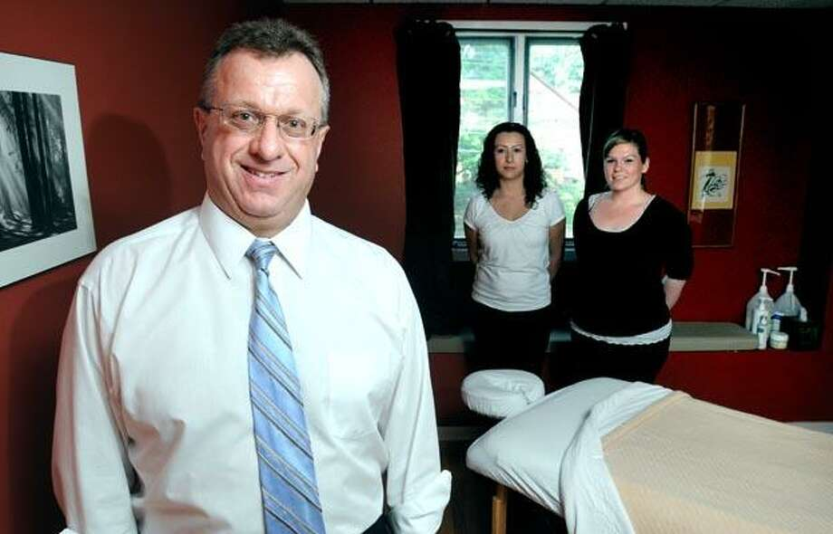 From left, Robert M. Denes and licensed massage therapists Elcy Pareja and Jessica Nieves-Diaz show off one of two massage rooms that Denes has added to his chiropractic business in Hamden. (Arnold Gold/Register)