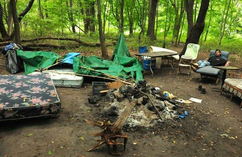 """An unidentified man sleeps in a chair in what remains of the """"tent city"""" after West Haven and New Haven authorities removed those who had been living there. Work to clean up the site is expected to begin today. (Brad Horrigan/Register)"""
