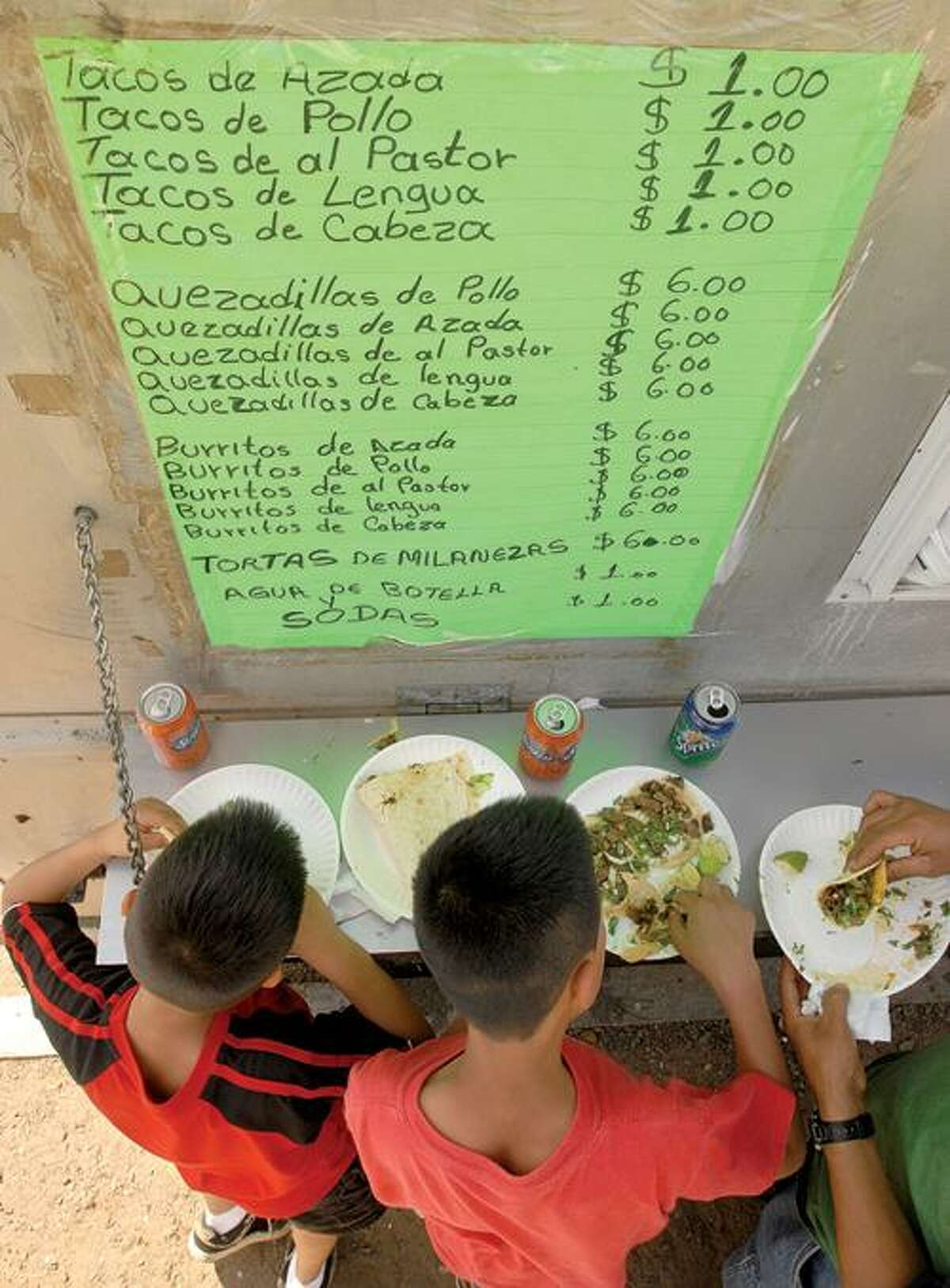 Two boys enjoy tacos at Ixtapa Mexican food truck on Long Wharf Drive. Register file photo