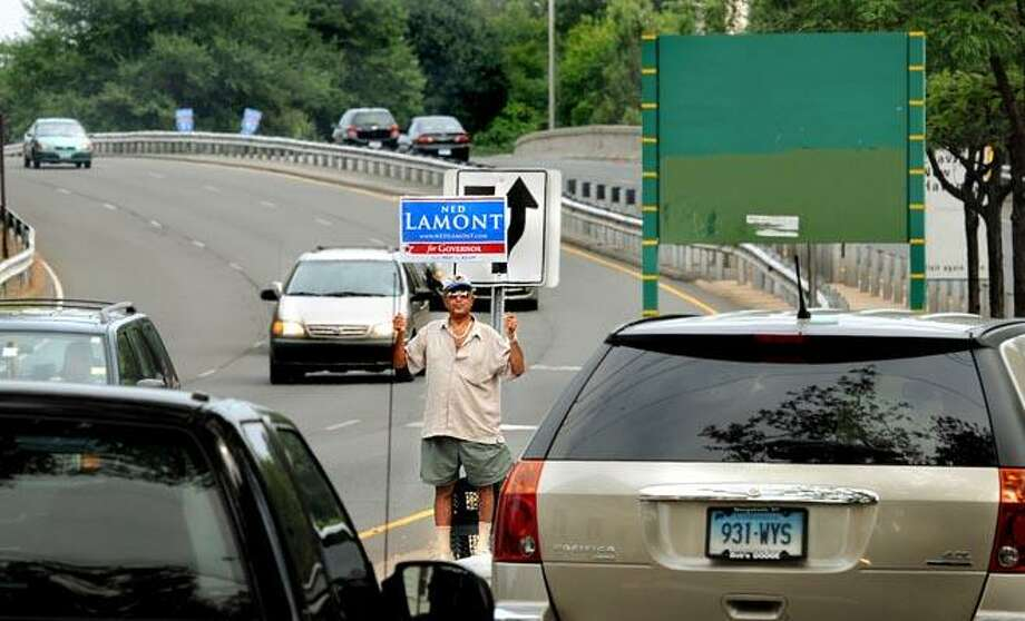 Bulent Ozalp of New Haven holds up a sign supporting Ned Lamont for governor, as he stands at the Interstate 91 entrance at the intersection of Trumbull and Orange streets Monday. Ozalp is a volunteer at Lamont's Orange Street office. (Melanie Stengel/Register)