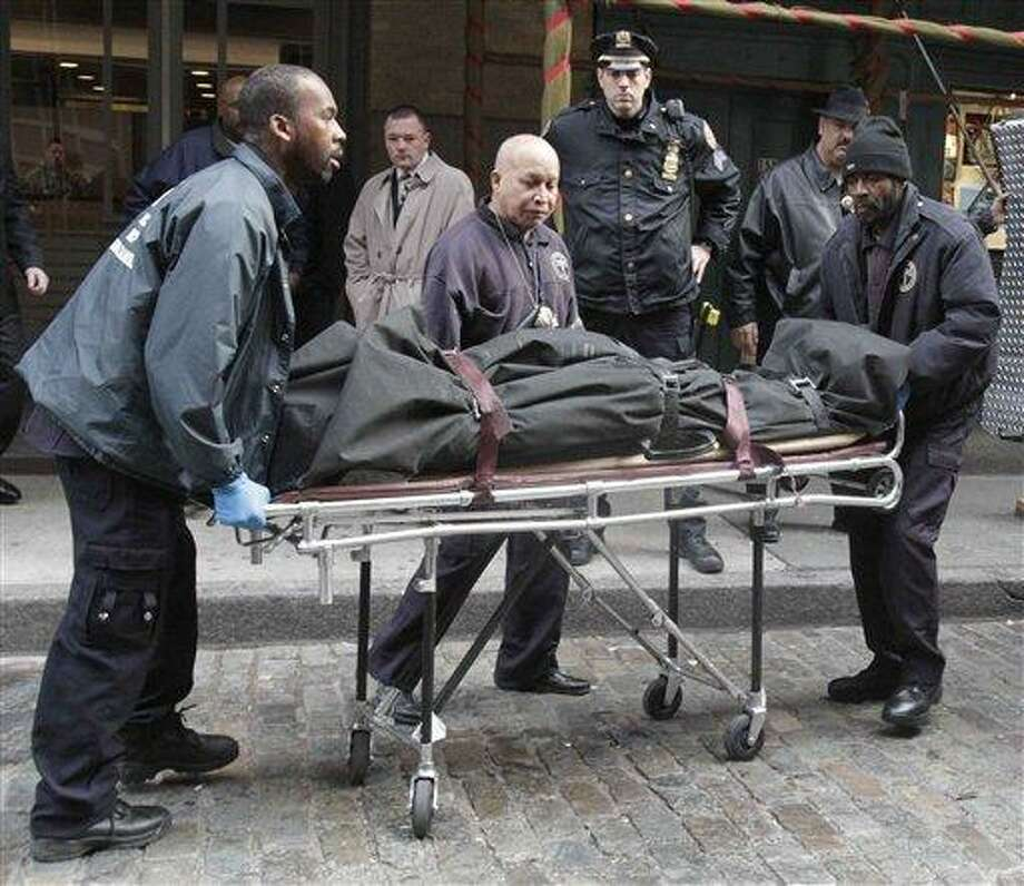 """Medical examiner staff remove the body of Mark Madoff from the apartment building in which he lived, Saturday, Dec. 11, 2010 in the Soho neighborhood of New York. Mark Madoff, the eldest son of disgraced financier Bernard Madoff, hanged himself by a dog leash in his apartment Saturday after two years of """"unrelenting pressure"""" following his father's arrest in a multibillion-dollar fraud that enveloped the entire family, law enforcement officials and a family attorney said. (AP Photo/Mary Altaffer) Photo: ASSOCIATED PRESS / AP2010"""