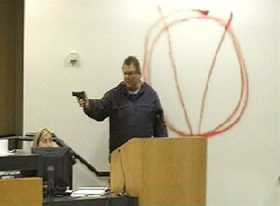 In this image taken from video and released by WJHG-TV, Clay A. Duke points a hand gun at Bay City school board members and staff, Tuesday, Dec. 14, 2010. Duke, a 56-year-old ex-convict, calmly held the school board at gunpoint and said he was seeking redress for his wife's firing before shooting at the superintendent at short range and then killing himself. (AP Photo/WJHG-TV) Photo: AP / WJHG-TV