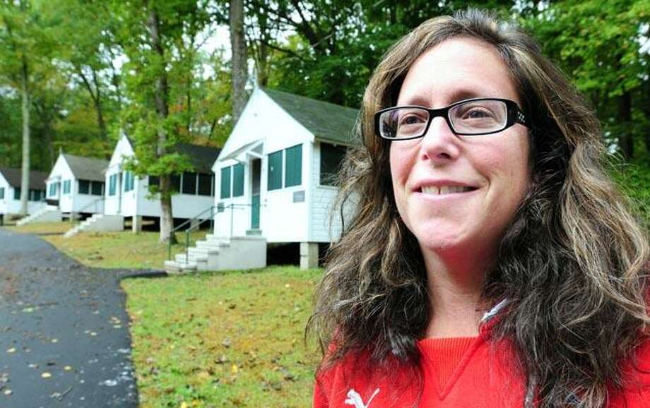 Ruth Ann Ornstein, executive director of Camp Laurelwood in Madison, stands in front of the renovated boys' campus cabins. (Arnold Gold/Register photos)