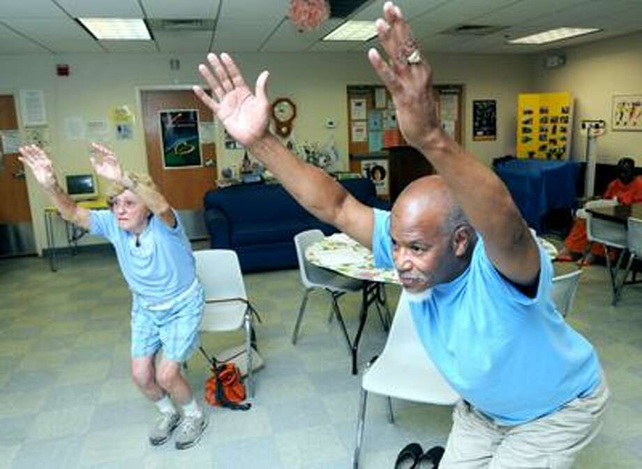 Jackie Collimore (left) and John Kittrell, Jr., (right) of New Haven take part in a yoga class for seniors a the Dixwell-Newhallville Senior Center in New Haven on 8/5/2010.Photo by Arnold Gold   AG0380B