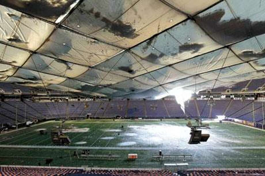 Snow falls onto the field from a hole in the roof of the Metrodome Sunday. The Minneapolis Vikings will face the New York Giants today at Detroit's Ford Field at 7:20 p.m. (AP Photo)