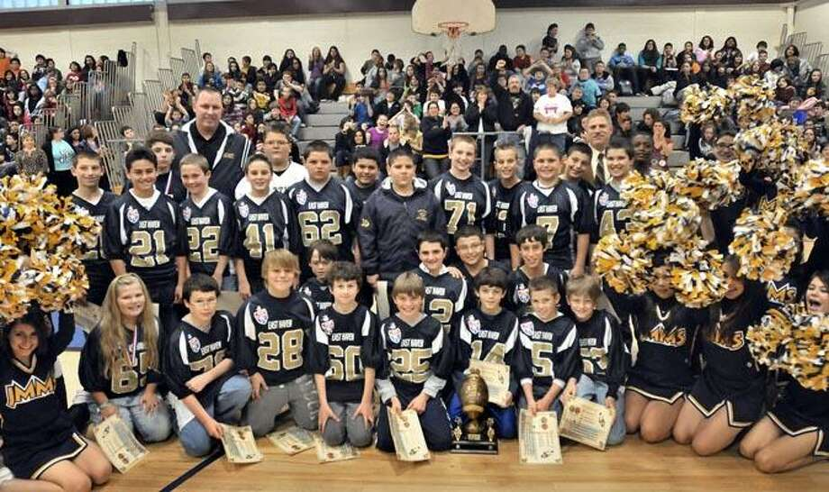 EAST HAVEN-Members of the Easties football team with their trophy. Friends, family, and community leaders honored the Easties at an assembly at Melillo Middle School in East Haven.     Melanie Stengel/Register12/13/10