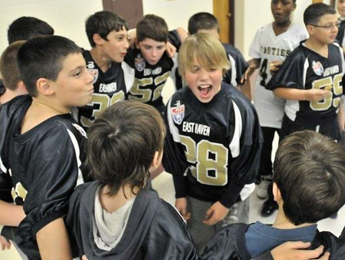 EAST HAVEN-Nick Spadacenta (C) leads teammates in a cheer. Friends, family, and community leaders honored the Easties at an assembly at Melillo Middle School in East Haven. Melanie Stengel/Register12/13/10