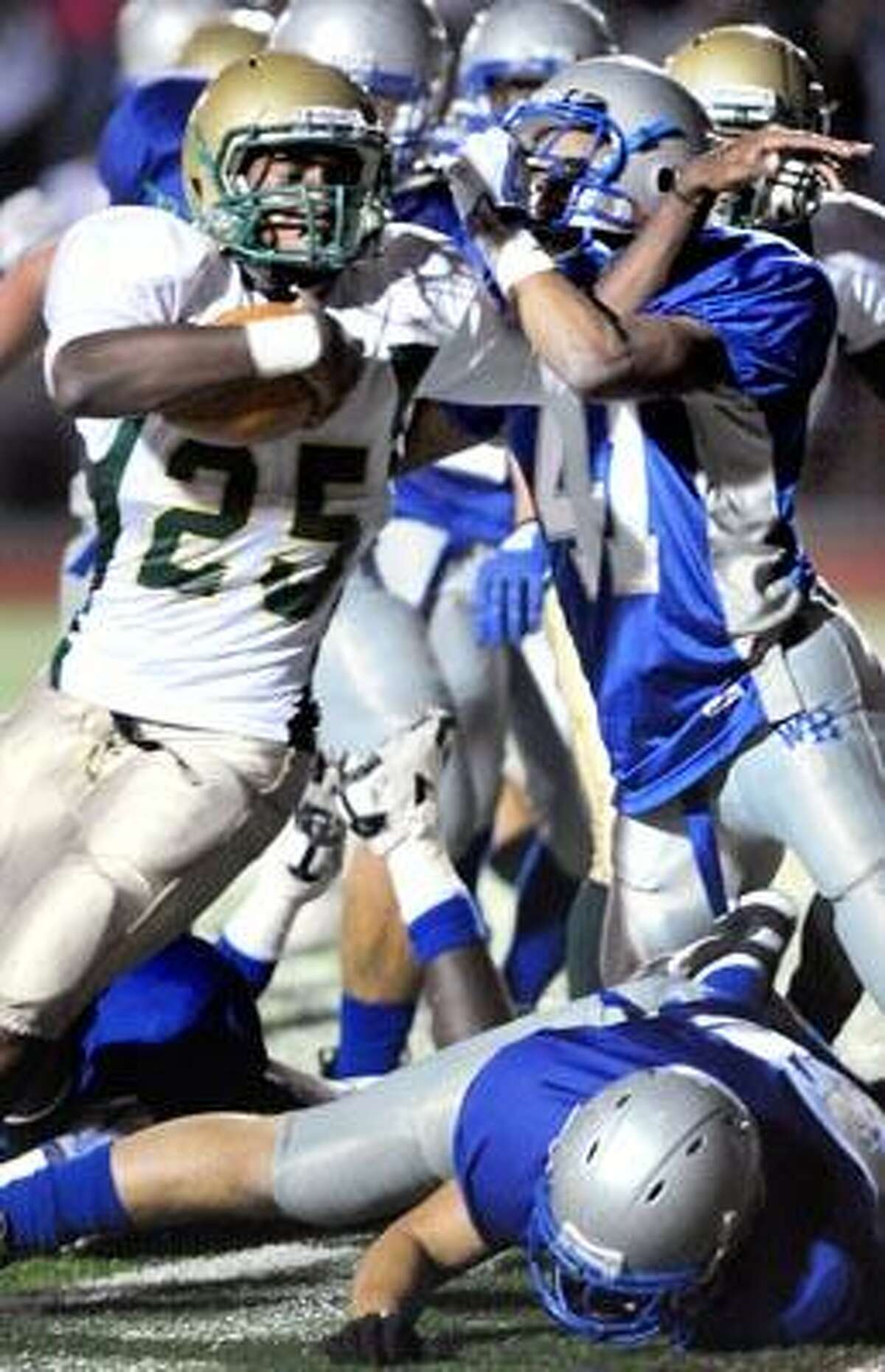 Notre Dame-West Haven's David Rose (25) is stopped by Andre Gee and the West Haven defense during first-half action in the Westies' 28-27 upset of the sixth-ranked Green Knights Friday night. (Arnold Gold/Register)