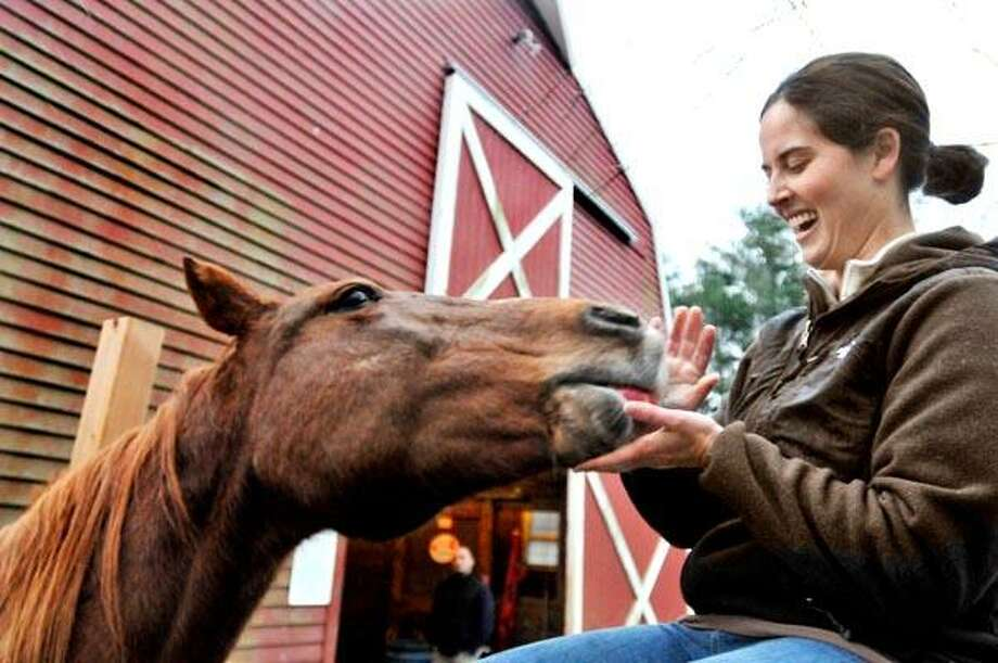 Northford---Mary Falcone, of Northford feeds an apple to June, one of the rescued horses at All the Kings Horses Equine Rescue.   Melanie Stengel/Register11/30/10
