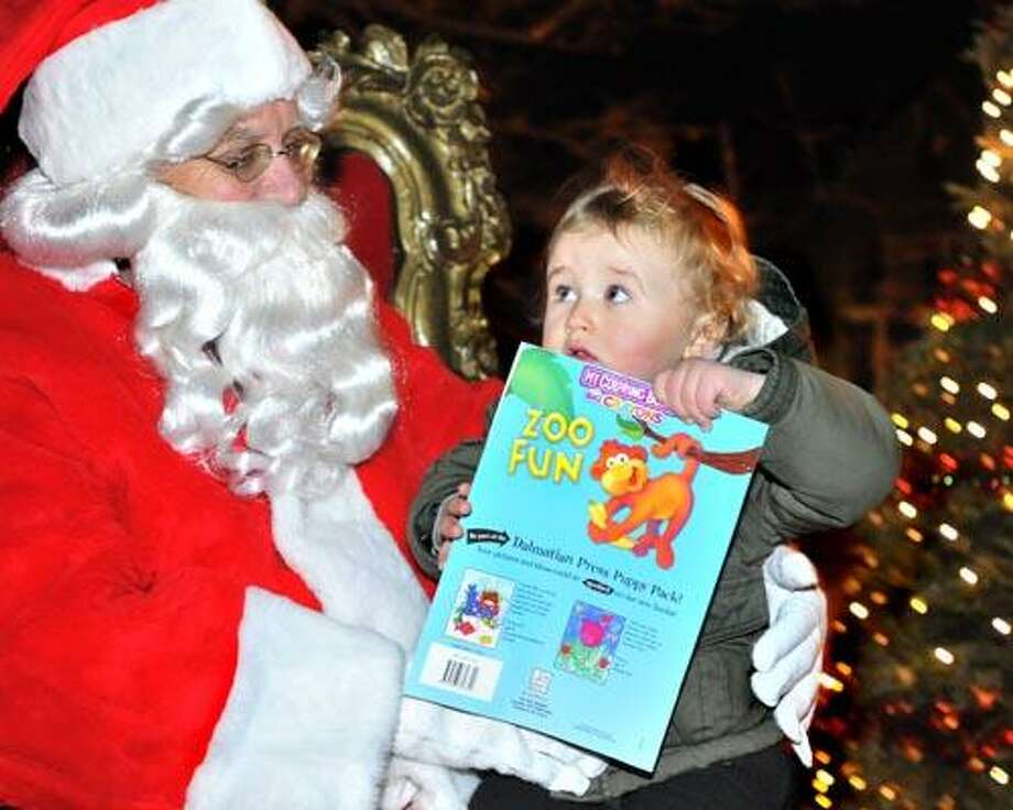 New Haven--Luca Ingles, 2, of New Haven, seems to be a little unsure of Santa, aka Bob Frew of the Upper State Association.   Ingles met Santa, who arrived by fire truck, at the Upper State Street Craft Fair and Tree Lighting festivities.   Melanie Stengel/Register12/11/10
