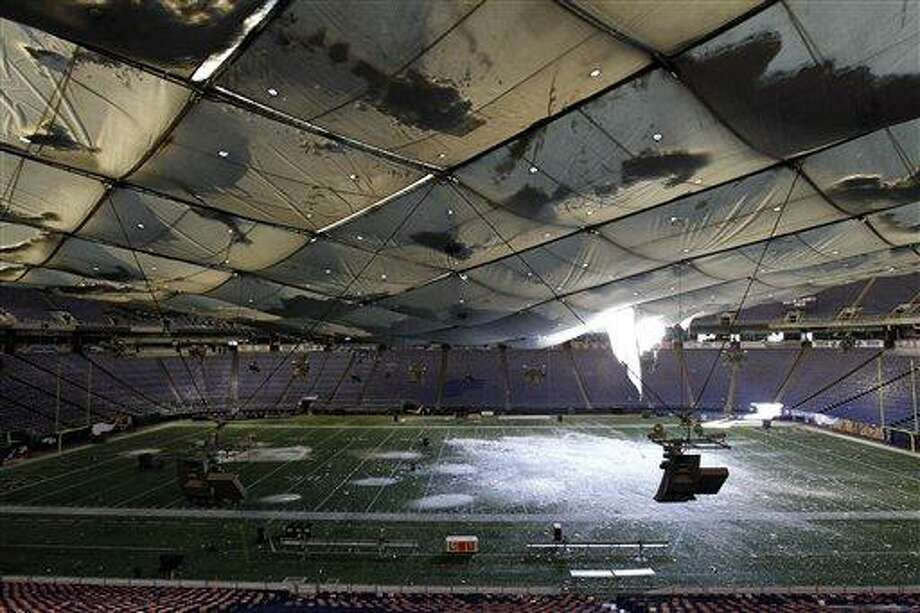 Snow falls into the field from a hole in the collapsed roof of the Metrodome in Minneapolis Sunday, Dec. 12, 2010.  The inflatable roof of the Metrodome collapsed Sunday after a snowstorm that dumped 17 inches (43 cms) on Minneapolis. No one was hurt, but the roof failure sent the NFL scrambling to find a new venue for the Vikings' game against the New York Giants. (AP Photo/Ann Heisenfelt) Photo: ASSOCIATED PRESS / AP2010
