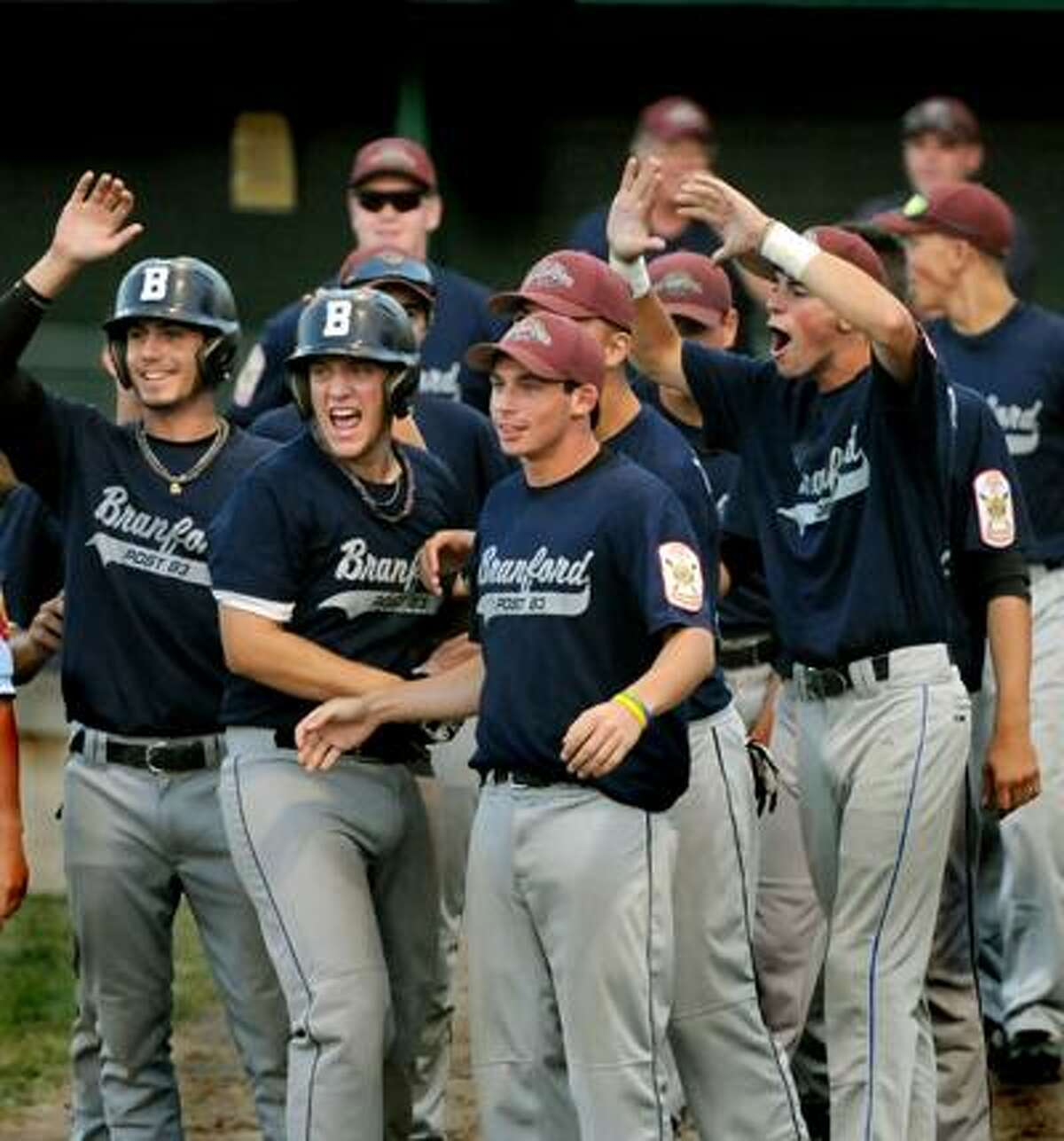 Members of the Branford American Legion team gather at home plate to welcome Michael Forgione (not pictured) after his two-run home run in the fourth inning of their 5-0 win over Goffstown (N.H.) Saturday night at Palmer Field in Middletown. (Melanie Stengel/Register)