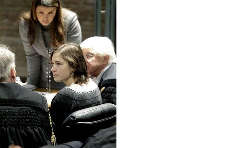 Amanda Knox, talks to her lawyer Carlo Della Vedova, left, with lawyers Maria del Grosso, background, and Luciano Ghirga, during a hearing in her appeals trial, at Perugia's courthouse, Italy, Saturday, Dec. 11, 2010. The 23-year-old American student was convicted of murder and sexual assault in the 2007 death of her flatmate, British student Meredith Kercher, and sentenced to 26 years in prison. (AP Photo/Pier Paolo Cito)