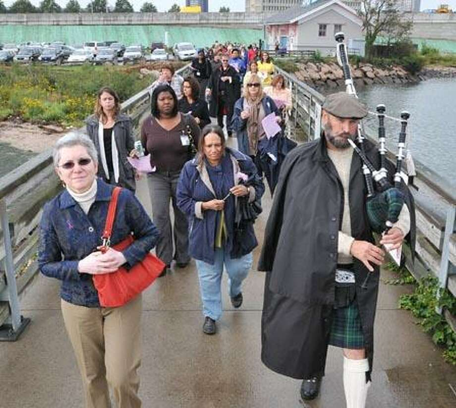 """Cas101006 Peter Casolino  10/06/10New Haven-- Sandra Koorejian, director of Domestic Violence Services of Greater New Haven and bagpiper Thomas Dalton of Milford lead a procession along the Long Wharf Pier during  the 11th annual """"Sound of Hope"""" remembrance ceremony.  Photo/Peter Casolino ***"""