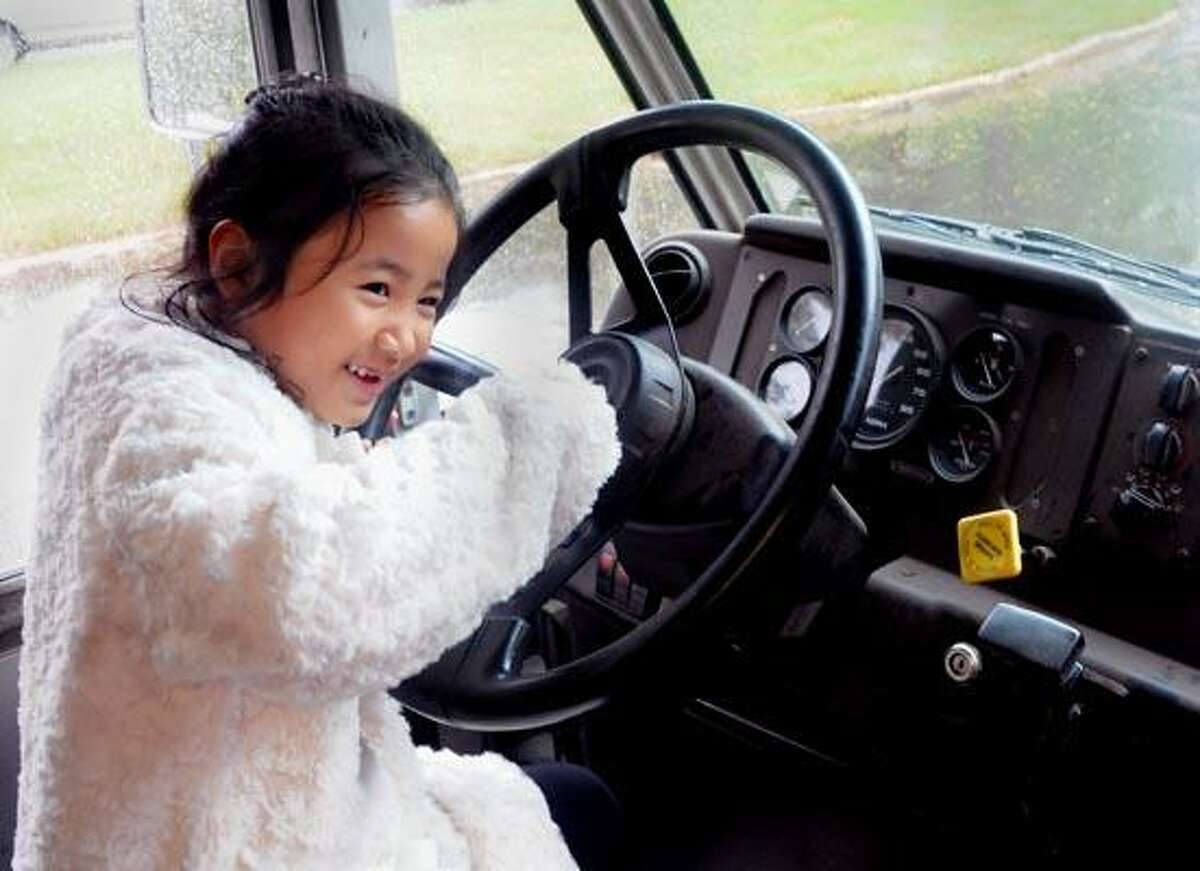 (ms101610)-Sally Kim, a first grader at Green Acres Elemenrary School in North Haven, beeps the horn of a Fed Ex truck during the school's