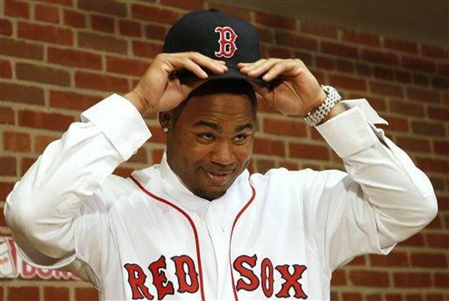 Carl Crawford tries on his new hat during a news conference announcing his signing by the Boston Red Sox baseball club at Fenway Park in Boston Saturday, Dec. 11, 2010. (AP Photo/Winslow Townson) Photo: AP / FR170221 AP