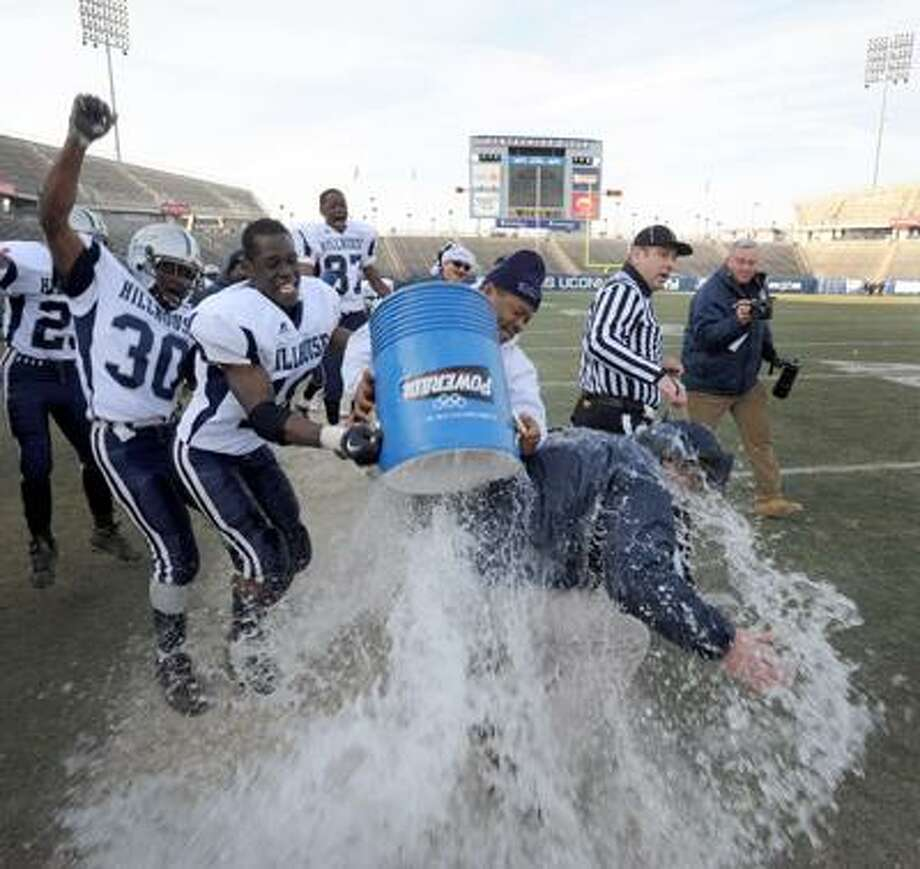 Hillhouse coach Tom Dyer gets soaked as the team celebrates their Class M state football championship win over New London on Saturday at Rentschler Field in East Hartford. Hillhouse won 7-0. (Peter Hvizdak/Register)