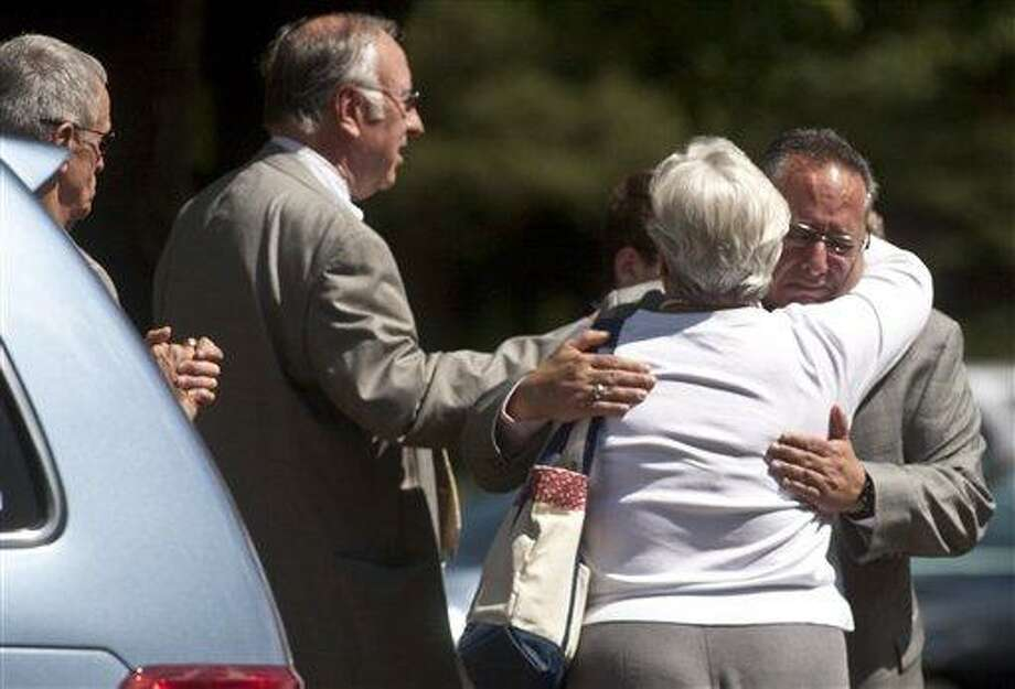 Steve Hollander, operations executive of Hartford Distributors, is embraced by neighbor Mary Bey while Larry Murphy stands beside them following funeral services for Craig Pepin at the St. Margaret Mary Church In South Windsor, Conn. on Aug. 7, 2010. Pepin was one of nine people killed during the Hartford Distributing shooting, and was preparing for retirement at the time of his death.(AP Photo/The Hartford Courant, Brooke LaValley) Photo: AP / HARTFORD COURANT