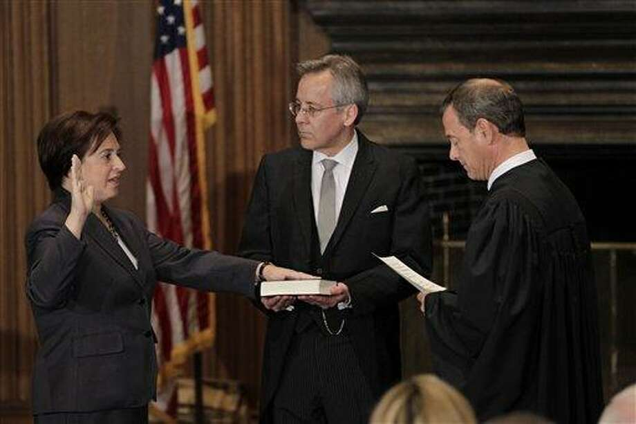Elena Kagan is sworn in as the Supreme Court's newest member as Chief Justice John Roberts, right, administers the judicial oath, at the Supreme Court Building in Washington, Saturday, Aug. 7, 2010. The Bible is held by Jeffrey Minear, center, counselor to the chief justice. Kagan, 50, who replaces retired Justice John Paul Stevens, becomes the fourth woman to sit on the high court, and is the first Supreme Court justice in nearly four decades with no previous experience as a judge. (AP Photo/J. Scott Applewhite) Photo: ASSOCIATED PRESS / AP