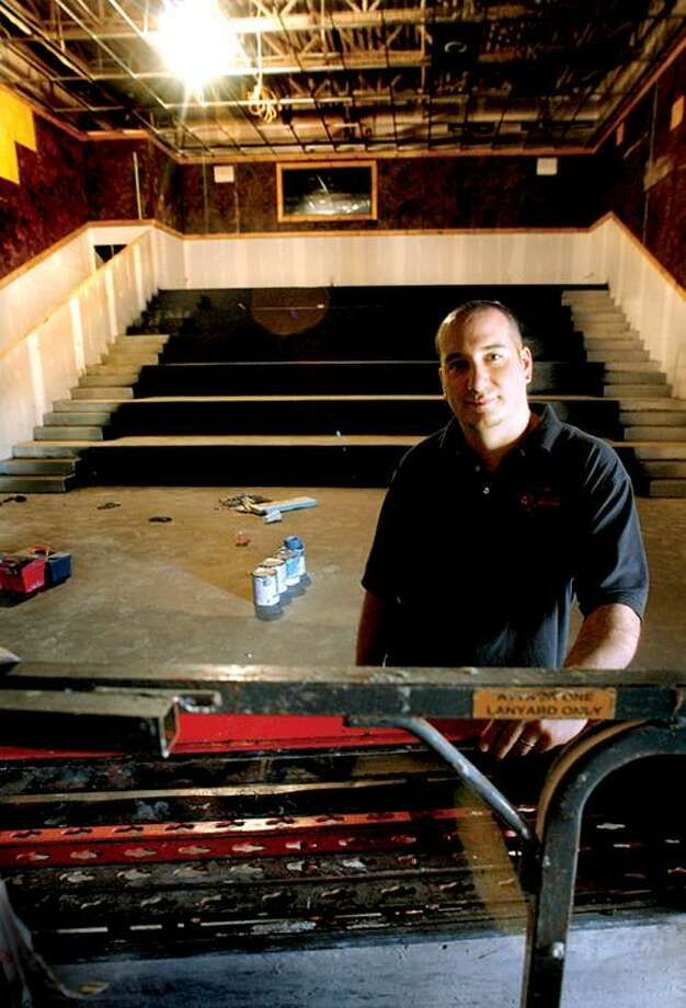 Kevin LaFlamme, of Holiday Cinemas in Wallingford, stands in what will soon be one of three new 100 stadium seat theaters added to the ten already at the complex.      Melanie Stengel/Register