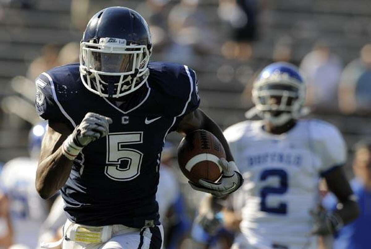 Connecticut's Blidi Wreh-Wilson returns an interception 46 yards for a touchdown as Buffalo's Marcus Rivers looks on during the second half of Connecticut's 45-21 victory in an NCAA football game in East Hartford, Conn., on Saturday, Sept. 25, 2010. (AP Photo/Fred Beckham)