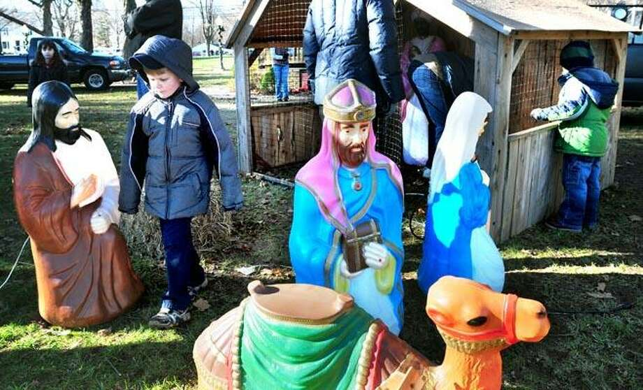 Christopher Carroll (left), 6, of Booth Hill School Cub Scout Pack 24 walks through Nativity figures being set up by the Cub Scouts and the Shelton Exchange Club on the Huntington Green in Shelton on 12/4/2010.Photo by Arnold Gold/New Haven Register     AG0395B
