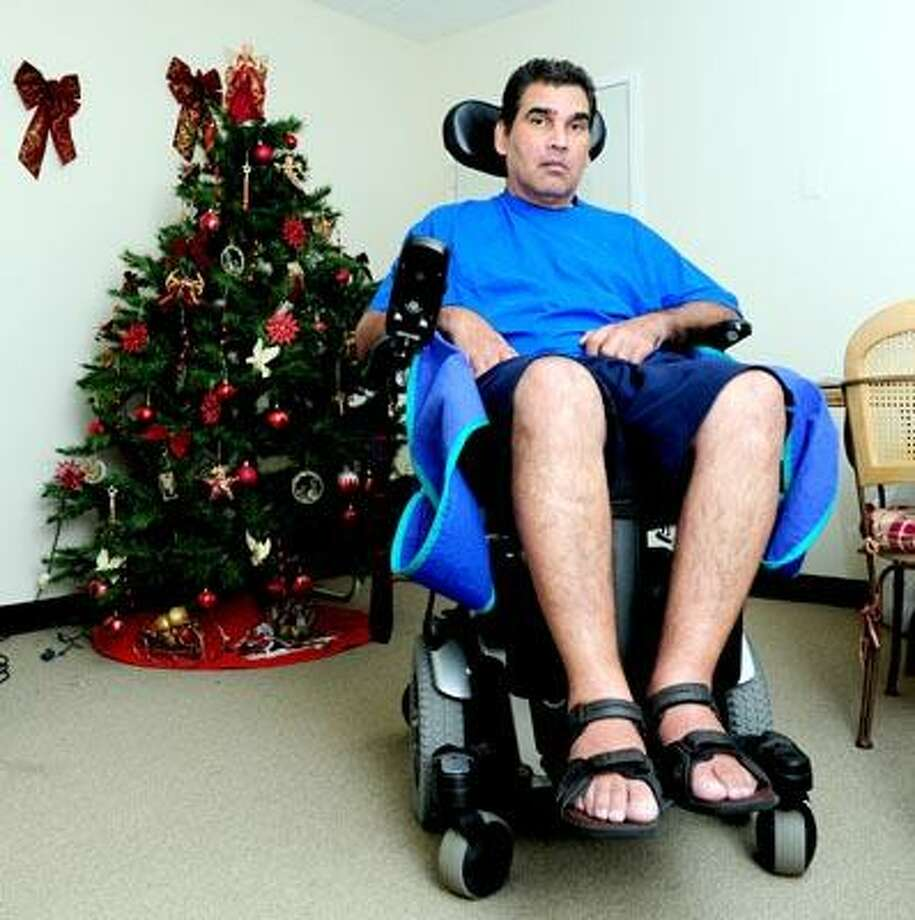 Gilberto Cosme, a victim of Lou Gehrig's disease, sits in the living room of his home on George Street in New Haven Thursday. Thieves stole his handicapped accessible van. (Arnold Gold/Register)