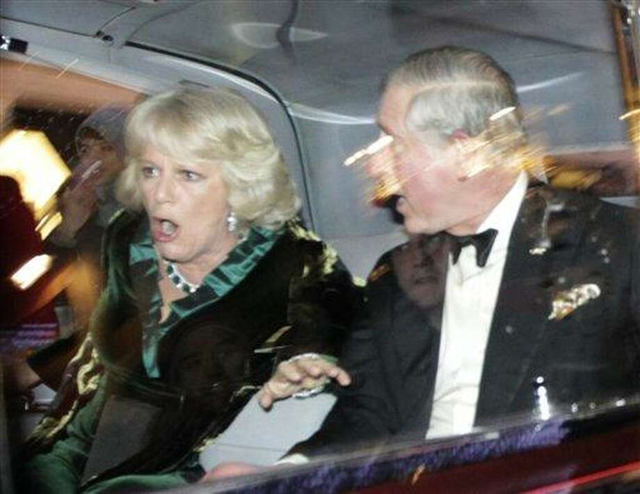 """Britain's Prince Charles and Camilla, Duchess of Cornwall, react as their car is attacked by angry protesters in London, Thursday, Dec. 9, 2010. An Associated Press photographer saw demonstrators kick the car in Regent Street, in the heart of London's shopping district. The car then sped off. Charles' office, Clarence House, confirmed that """"their royal highnesses' car was attacked by protesters on the way to their engagement at the London Palladium this evening, but their royal highnesses are unharmed."""" (AP Photo/Matt Dunham) Photo: AP / AP"""