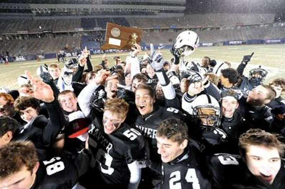 No. 1 Xavier celebrates its 24-13 victory over third-seeded Trumbull for the Class LL state championship Friday night at Rentschler Field in East Hartford. (Peter Casolino/Register)  12/10/10 Cas101210