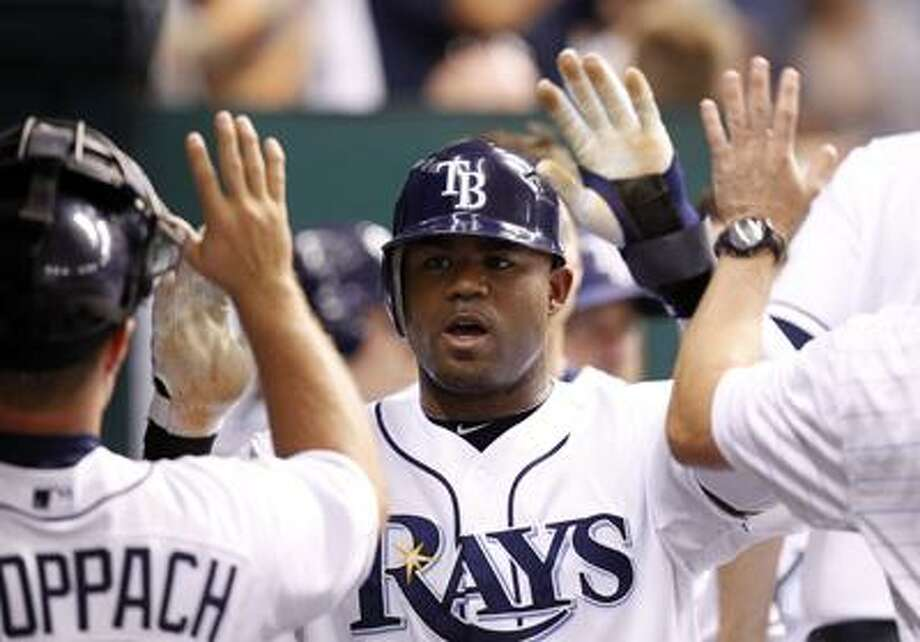 FILE - This July 27, 2010, file photo shows Tampa Bay Rays' Carl Crawford being congratulated after scoring in the sixth inning of the Rays' 3-2 victory over the Detroit Tigers in a baseball game in St. Petersburg, Fla.  Crawford has reached a preliminary agreement with the Boston Red Sox on a $142 million, seven-year contract, a person familiar with the negotiations told The Associated Press. The agreement is subject to Crawford passing a physical, the person said Wednesday night, Dec. 8, 2010.(AP Photo/Mike Carlson, File) Photo: AP / Mike Carlson Photography