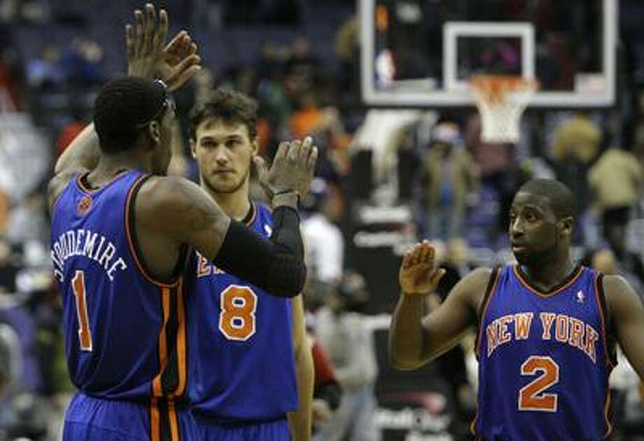 New York Knicks teammates Amare Stoudemire (1), Danilo Gallinari (8), and Raymond Felton (2) congratulate each other on their win against the Washington Wizards at an NBA basketball game at the Verizon Center in Washington on Friday, Dec. 10, 2010.  The Knicks won 101-95, in their longest winning streak in nearly a decade. (AP Photo/Jacquelyn Martin) Photo: AP / AP