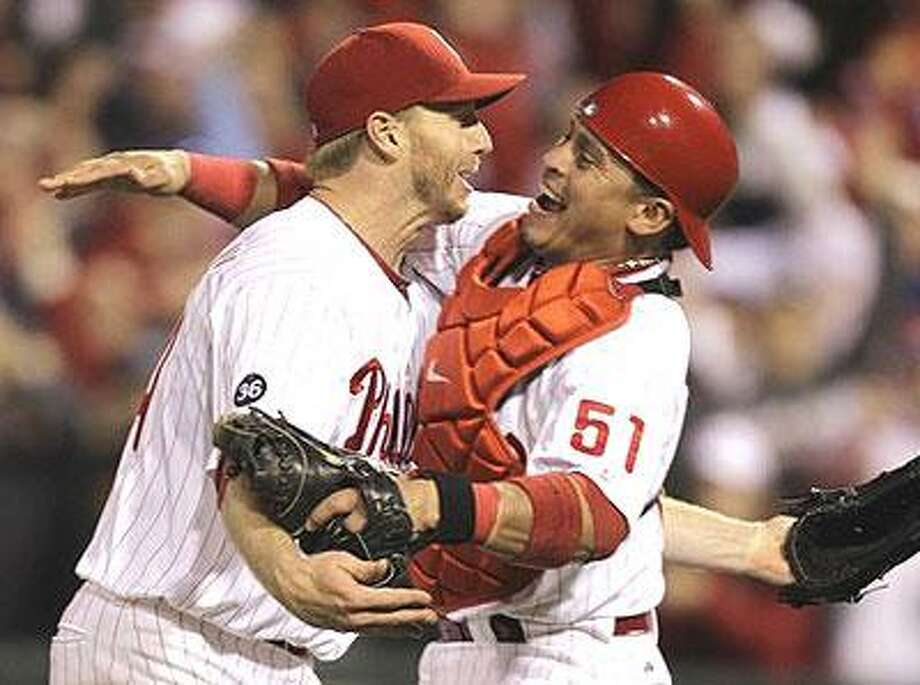 Philadelphia Phillies starting pitcher Roy Halladay, left, celebrates with catcher Carlos Ruiz (51) after throwing a no-hitter to defeat the Cincinnati Reds 4-0 during Game 1 of baseball's National League Division Series, Wednesday, Oct. 6, 2010, in Philadelphia. (AP Photo/Rob Carr)