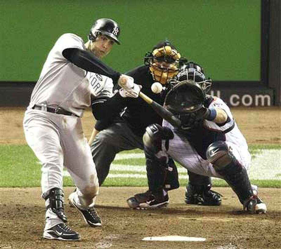 New York Yankees' Mark Teixeira hits a two-run home run during the seventh inning of Game 1 of baseball's American League Division Series against the Minnesota Twins on Wednesday, Oct. 6, 2010, in Minneapolis. (AP Photo/Paul Battaglia)