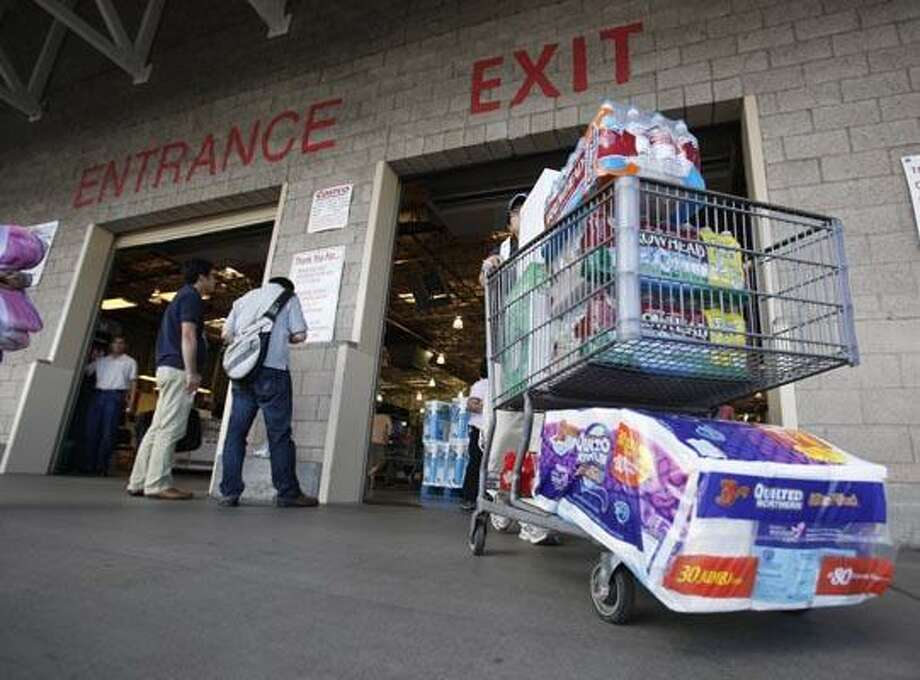 In this Sept. 8, 2010 photo, a Costco customer leaves Costco in Mountain View, Calif. A trade group said Tuesday, Oct. 5, 2010, U.S. service-oriented companies, the nation's predominant job generator, grew slightly faster in September as demand from customers improved. (AP Photo/Paul Sakuma) Photo: AP / AP
